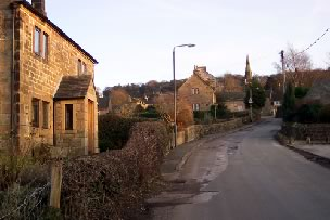 Image: The main street of Stanton in Peak, Derbyshire, illuminated by the soft evening light.